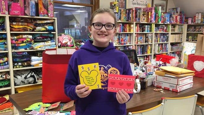 Olivia Dudas poses with two of the handmade valentines she collected for patients at nursing facilities and Riley Hospital for Children.