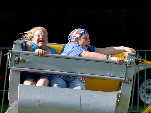 One rider laughs as the other holds on and lets out a yell while they ride the Scrambler together on the midway at this year's America's Birthday Celebration in Gypsy Hill Park on Friday, July 4, 2014.