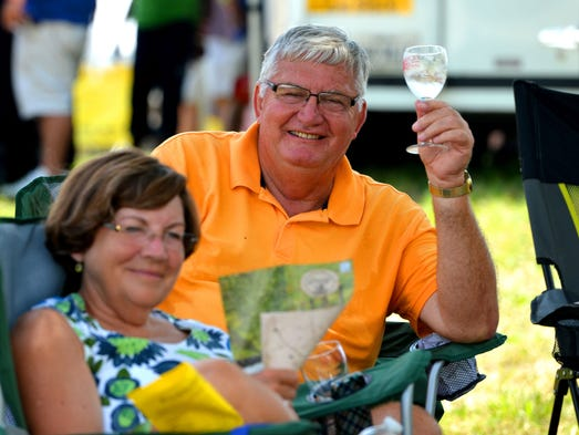Sitting in the shade of a tree, Denzil Valentine of Pennsylvania raises a glass of wine as he sits with his wife, Patty Valentine. They enjoy the first day of the Daylily Food & Wine Festival at the Andre Viette Farm and Nursery in Fishersville on Saturday, July 20, 2013.