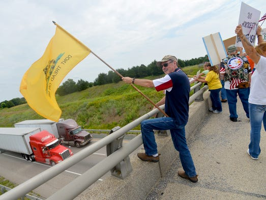 """Terry Adams of Churchville holds onto a """"Don't Tread On Me"""" flag. He joins about 50 people who came to the Va. 612 overpass in Verona on Saturday morning, July 19, 2014. They gather to demonstrate for and against various immigration issues, drawn by news that an Augusta County center hosts several undocumented children."""