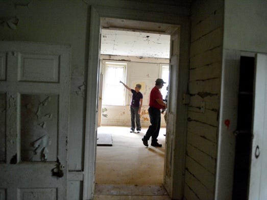 Assistant to the county administrator, Candy Hensley points out something on one wall to a a member of the media as John Cook of the maintenance department crosses the room. Normally closed up, the circa 1830 brick home known as Grandma Moses house, or Mount Airy, was opened briefly during a media interview in Verona on Tuesday, Aug. 19, 2014.