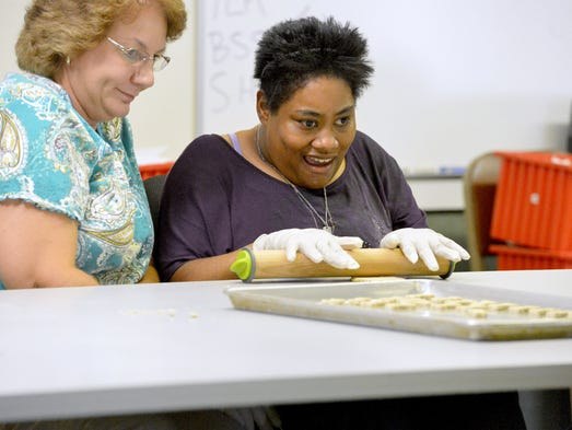 """Program participant Carmen Connors rolls out dough which will be cut into doggie biscuits for baking with the help of day support specialist Paula Robinson. They help create doggie biscuits at Valley Community Services Board's Orchard Hill Day Support in Staunton on Friday, August 22, 2014. It's part of their """"Bow Wow Biscuits"""" which the sell as part of their program."""