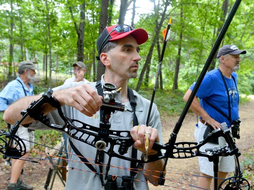 Dave Pyle of Goochland County looks to the target while making adjustments to his bow before taking his next shot. He joins friends following the designated course of targets during Augusta Archers 3-D archery shoot near Staunton on Saturday, August 23, 2014. The event continues Sunday.