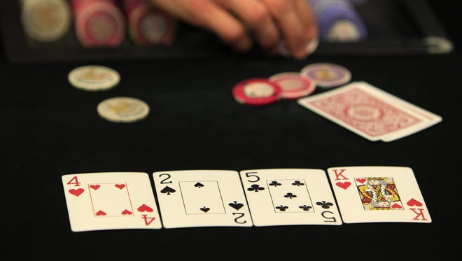 A poker dealer is works a game at the Magic City Casino in Miami.