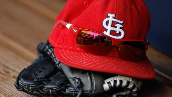 Detailed view of St. Louis Cardinals cap and glove in the dugout before a game.
