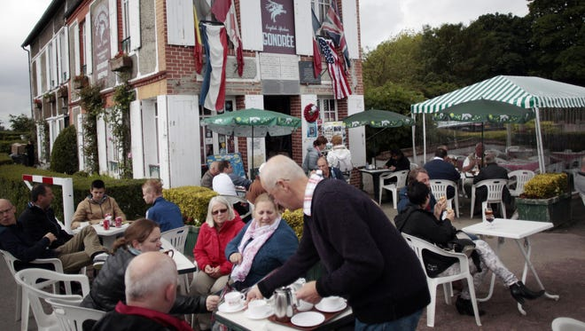 Tourists sit at café Gondrée, the first continental house liberated in 1944, on May 31, 2014, in Benouville, northwestern France.