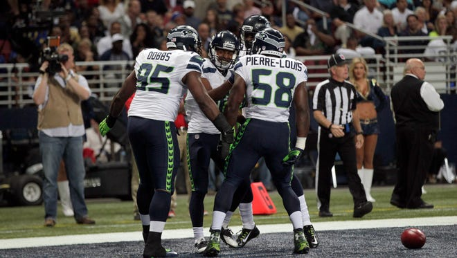 Seattle Seahawks wide receiver Tyler Lockett, second from left, is congratulated by teammates after scoring on a 57-yard punt return during the first quarter of an NFL football game against the St. Louis Rams Sunday, Sept. 13, 2015, in St. Louis.