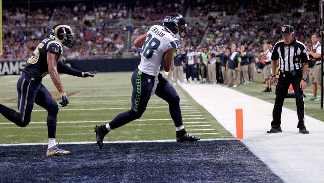 Seattle Seahawks tight end Jimmy Graham, right, catches a 7-yard touchdown pass as St. Louis Rams strong safety T.J. McDonald watches during the fourth quarter of an NFL football game Sunday, Sept. 13, 2015, in St. Louis.