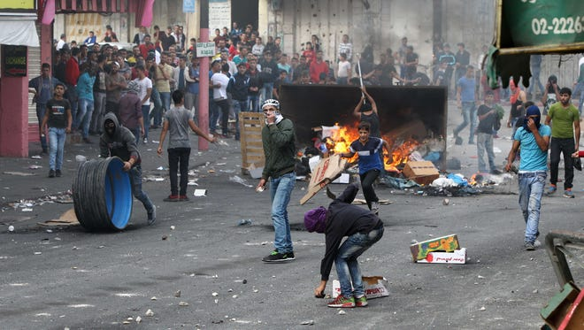 Palestinians clash with Israeli security forces near an Israeli checkpoint in the West Bank town of Hebron on Oct. 6, 2015.