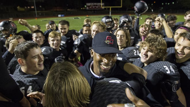 Boulder Creek assistant coach Jumanne Robertson (center) celebrates his wedding proposal to his girlfriend of five years after Friday's win over Horizon.