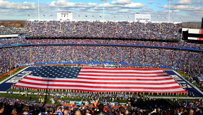 A large American flag covers the entire field at Ralph Wilson Stadium as the NFL honors veterans for Veterans Day.