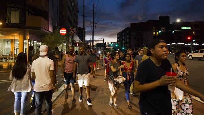 Pedestrians walk along Roosevelt Street during First Friday on Roosevelt Row in Phoenix in August.
