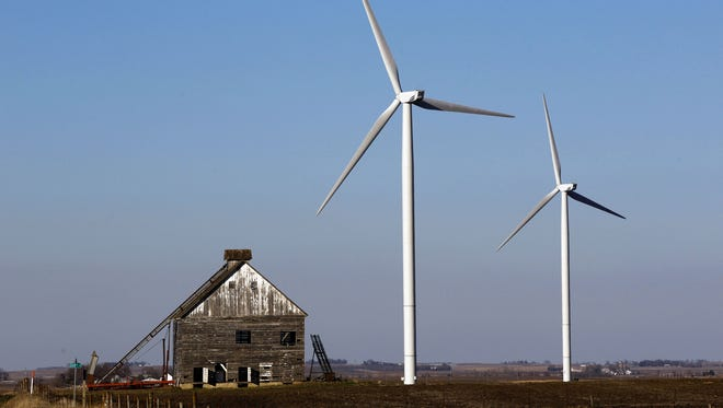 A pair of wind turbines tower over a barn at a wind farm near Rippey.