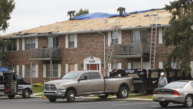 Roofers tarp a two-story apartment on Country Squire Court, where one of their co-workers, Alberto Dominguez, 33, fell to his death earlier Thursday.
