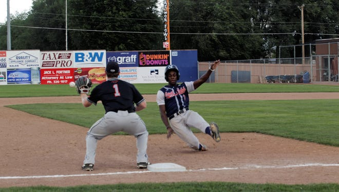East Cobb's Ryan Bliss slides in to third base ahead of the tag from Texas Stix's Lance Russell on Sunday at Ricketts Park.