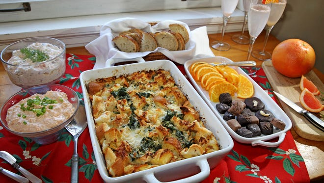 This New Year's brunch features spinach and cheese strata (center), sun-dried tomato dip, smoked trout salad (top left) and grapefruit mimosas.