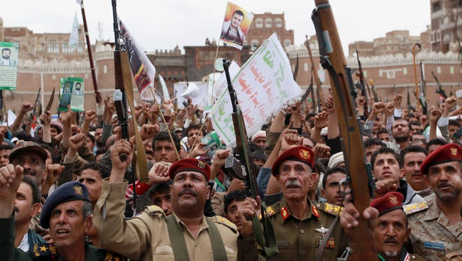 Shiite rebels, known as Houthis, hold up their weapons to protest against Saudi-led airstrikes, during a rally in Sanaa, Yemen, on March 26, 2015.