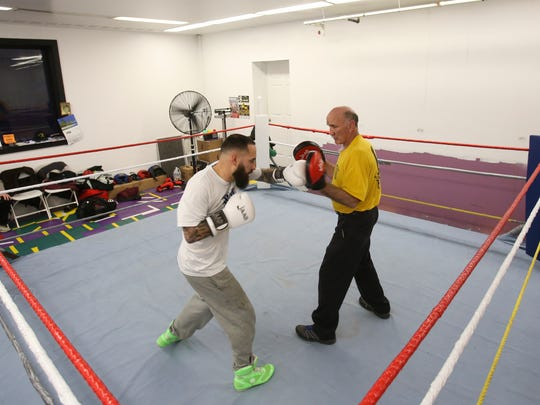 Joe Tiberi (right) works out his son, pro boxer Joey Tiberi, at his boxing gym in the Delaware Swim and Fitness Center in Pike Creek.