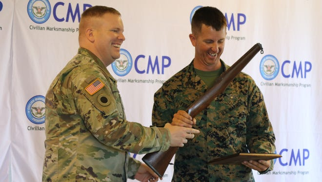 Staff Sgt. Stephen Ferguson, right, of the U.S. Marine Corps, won first place in the Roosevelt Commemorative Match on Tuesday. Capt. Michael Yates, left, base operations supervisor of Camp Perry, presented Ferguson his award.
