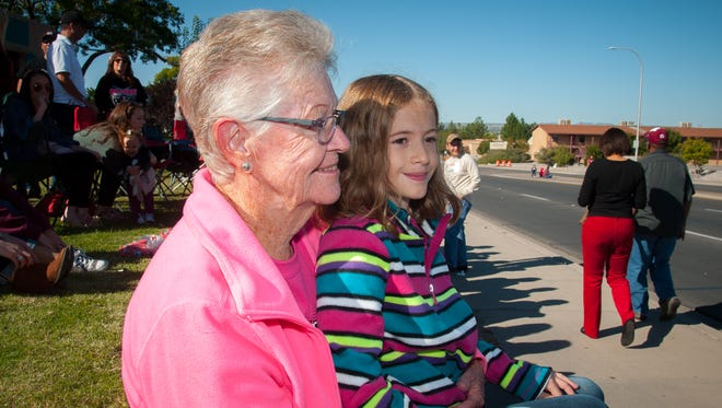NMSU alumna Carolynn Henry, who graduated in 1963, watches the homecoming parade on University Avenue with her 9-year-old granddaughter, Kathleen Hobbs.