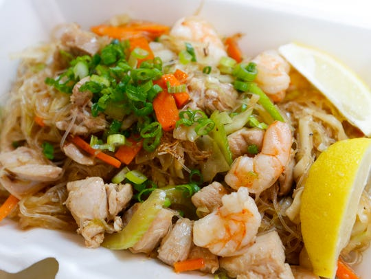 A Filipino dish of pancit in a to-go box at the Exotic