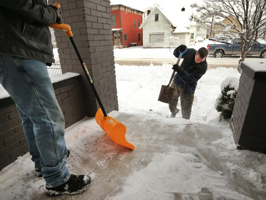 (From left) Michael Parr of Indianapolis and Paul Box of Brownsburg work on shoveling snow and ice off the front porch and sidewalk of a friend on Wednesday, January 8, 2014 as weather conditions begin to improve around the city and surrounding counties.