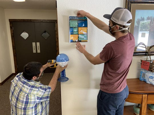 Mount Shasta First Baptist Church pastor Brandon Turk, left, and pastor Alastair Curley work to install a new hand sanitizing station at the Mount Shasta church in preparation for their first in-person service in more than two months, planned for June 7.