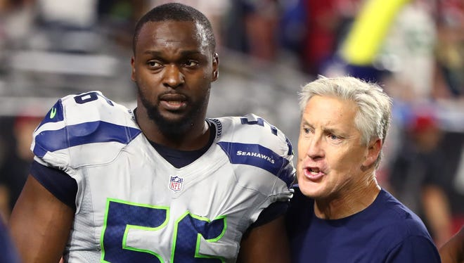 This file photo from 2016 shows Seahawks defensive end Cliff Avril and coach Pete Carroll after a game against the Cardinals at University of Phoenix Stadium in Glendale, Ariz.
