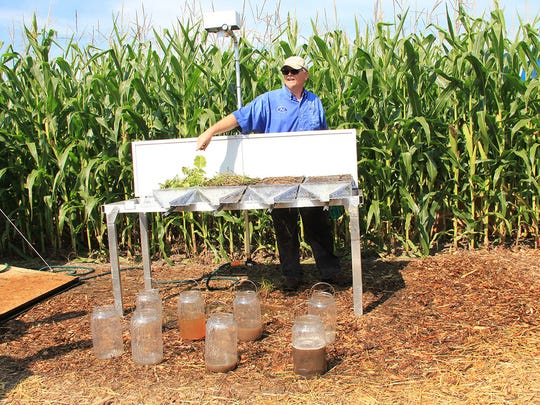 Pat Lake, NRCS Soil Conservationist, Oshkosh Service Center, discusses the rainfall simulator. The left sample includes cover crops planted with no-till which had little runoff and great water infiltration. The right sample was conventionally tilled with no active root causing runoff and little water infiltration.