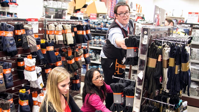 Towne East J.C. Penney employees, from left, Tori Goldsmith, Carla Fuller and Brian Hill stock men's socks as they prepare for Thanksgiving Day sales, in Wichita, Kan.