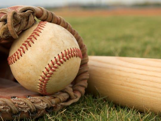 A baseball in a glove and baseball bat laying in grass.