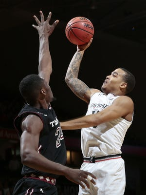 Cincinnati Bearcats' Troy Caupain tosses in a shot over Temple Owls center Ernest Aflakpui (24) in the second half.