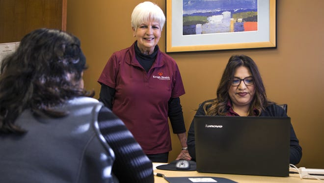 Saundra Johnson (center), executive director of Keogh Health Connection in Phoenix, talks with a client (left) as navigator Veronica Rivas processes information.