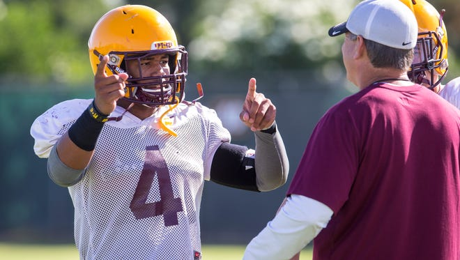 Arizona State linebacker D.J. Calhoun (4) talks with coaches during fall practice on Aug. 4, 2014, at the Kajikawa Football Practice Field in Tempe. The Sun Devil's first game is against Weber State at home on Aug. 28.