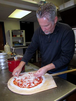 Owner David Grasso prepares a pizza at his Horseheads restaurant, Louciano's.