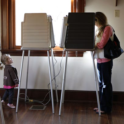 Sophie Horst, 2, from Mt. Lookout, peeks up at a voting