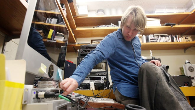 Chris Segura, an archivist in the Archives of Cajun and Creole Folklore at UL, plays an old analog recording.