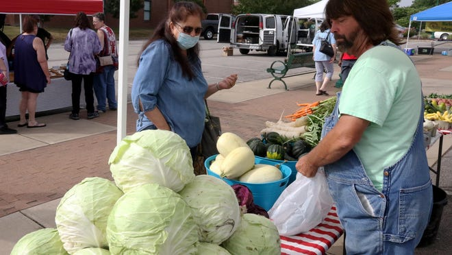 Tammy Todd of Barling looks to pick up some fresh vegetables from David Reynolds, Saturday, June 27, 2020, during a trip to the Fort Smith Farmers Market on Garrison Avenue.