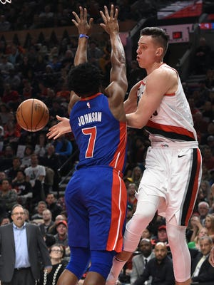 Portland Trail Blazers center Zach Collins passes the ball as Detroit Pistons forward Stanley Johnson defends during the second half of an NBA basketball game in Portland, Ore., Saturday, March 17, 2018. The Blazers won 100-87.