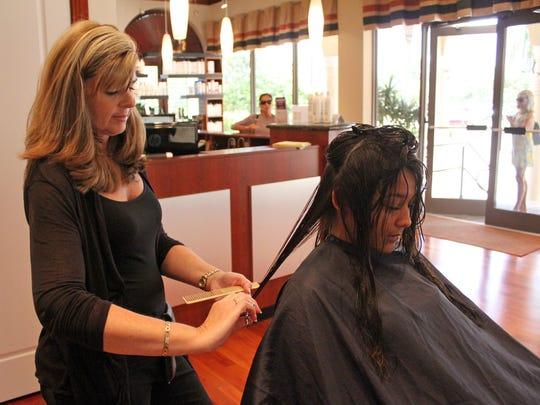 Hairdresser Diane Trzyna trims Michelle Moriggia's hair at Rick's Island Salon & Day Spa.