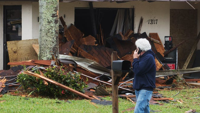 A man walks by a building damaged by a tornado that hit in south Fort Myers at a Camelot Drive apartment complex.