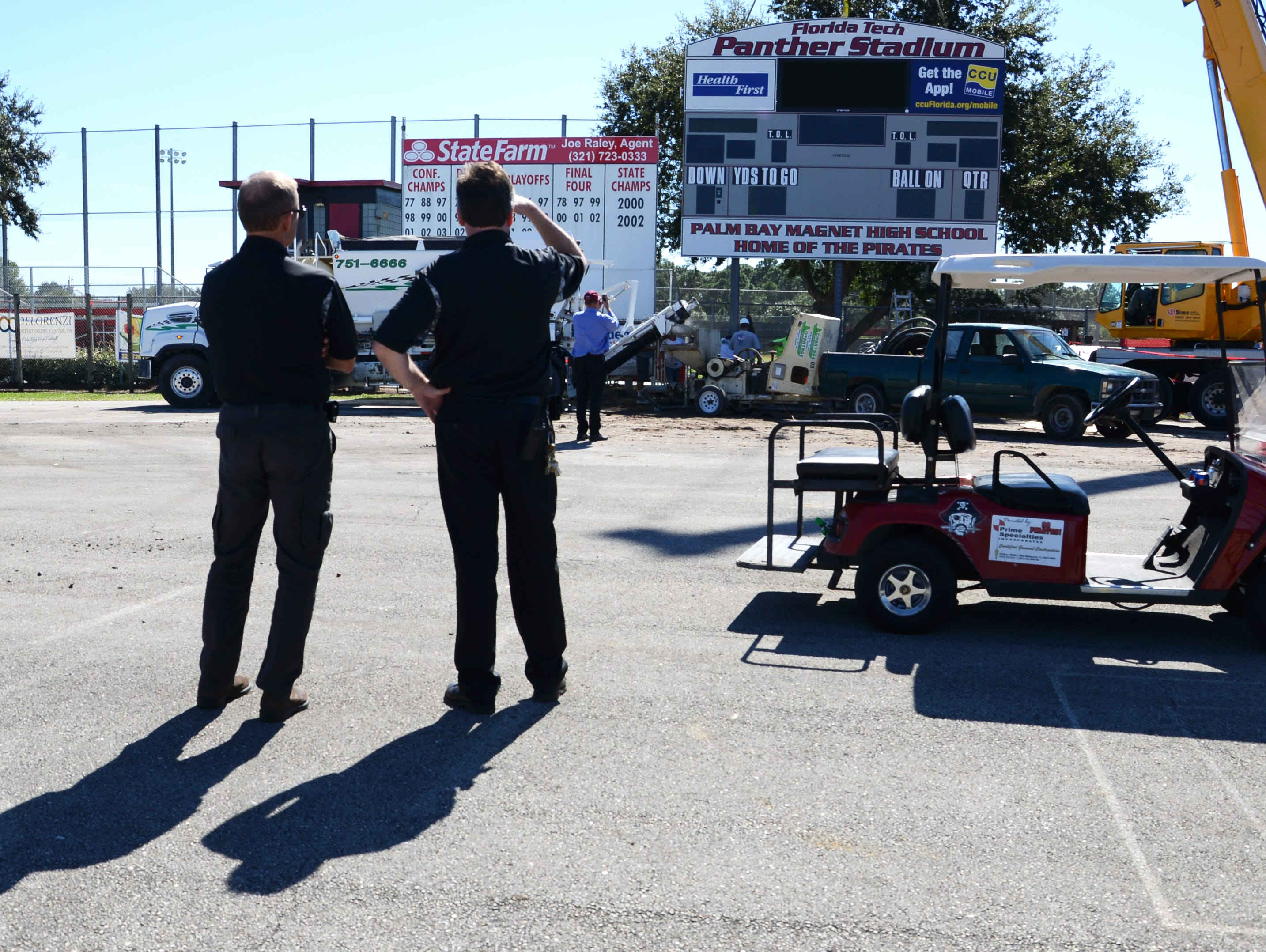 Palm Bay High officials watch as workers install the new scoreboard sign at Panther Stadium in Melbourne Friday.
