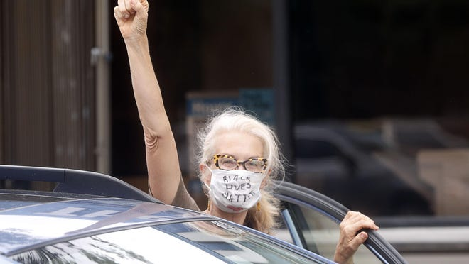 A woman shows support for a group of people taking part in a George Floyd protest that began at West Palm Beach city hall and then weaved its way around the downtown area for several hours on Tuesday.