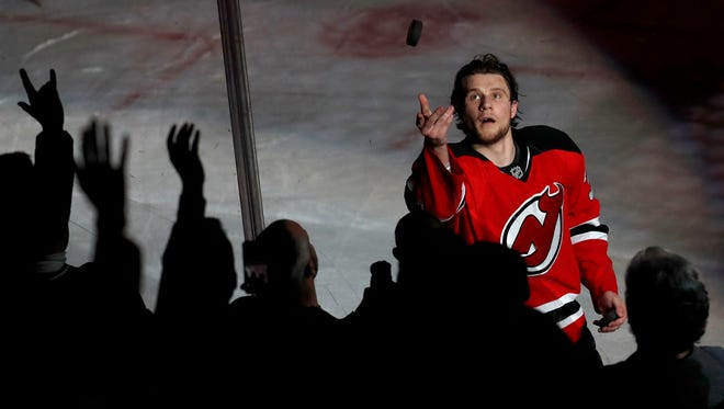 Devils center Pavel Zacha throws a puck toward fans after the Devils beat the Colorado Avalanche, 3-2, in an NHL hockey game, Tuesday, Feb. 14, 2017, in Newark, N.J. The Devils won 3-2.