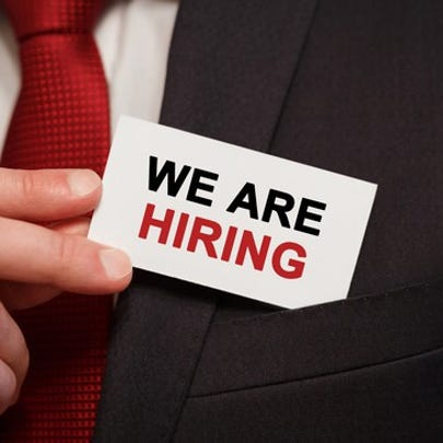 """Businessman holding card stating """"We are hiring"""""""
