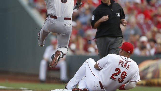 Cincinnati Reds first baseman Brayan Pena (29) dives back into first base, after running wide fielding the ball, to make the force out of Arizona Diamondbacks left fielder David Peralta (6), during the first inning.