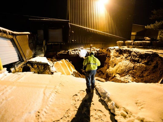 A Pennsylvania American Water employee inspects a large sinkhole that opened up on the property of Philadlephia Mixing Solutions in Palmyra on Sunday, Feb. 10, 2014. The sinkhole caused at least one building to partially collapse.