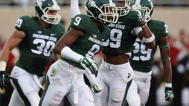 Michigan State players celebrate after a tackle during first quarter action against Jacksonville State on Aug. 29, 2014 at Spartan Stadium.