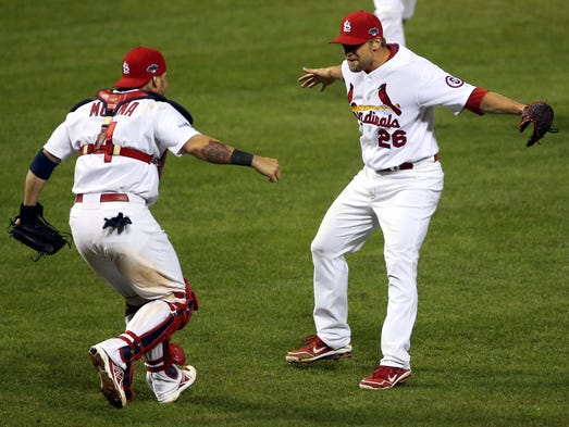 Game 6 -- Cardinals 9, Dodgers 0: Trevor Rosenthal (26) and Yadier Molina (4) celebrate after recording the final out to clinch the National League pennant.