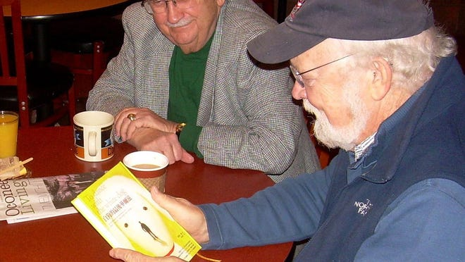 """Author Terry Kay, right, and his friend, Wally Eberhard, have coffee a few years back as they look over a Japanese edition of Kay's """"To Dance With the White Dog.""""  Eberhard, a University of Georgia journalism professor, died in 2018."""